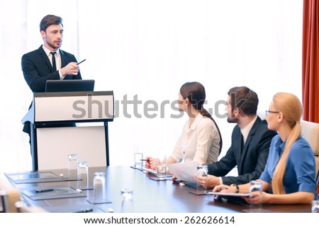 Business reporting at meeting. Young handsome business professional standing at the tribune makes report to his colleagues  - stock photo