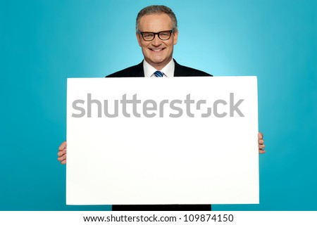 Business representative holding blank ad board and smiling at camera - stock photo