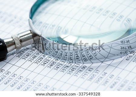Business research. Closeup of magnifying glass on paper with digits - stock photo