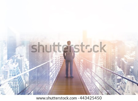 Business risk and research concept with back view of businessman standing on suspended bridge above New York city and looking into the distance. Toned image, 3D Rendering - stock photo