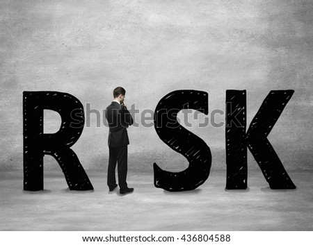 Business risk concept with thoughtful businessman standing instead letter I on concerete background - stock photo