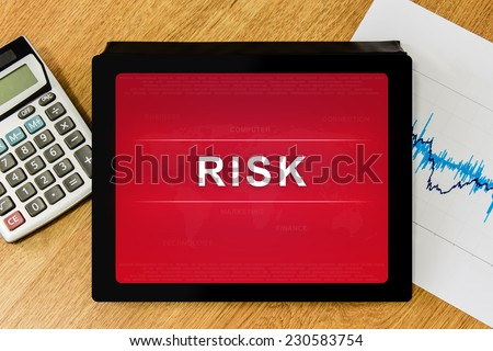 business risk word on digital tablet with calculator and financial graph - stock photo