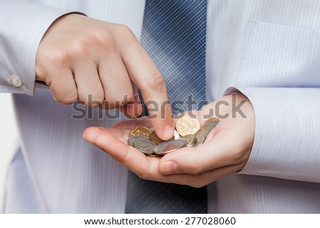 Business risks and finance issues concept - businessman hand holding coin savings counting money profit or losses - stock photo