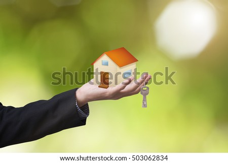 business salesman hand holding home and home key concept home sale.