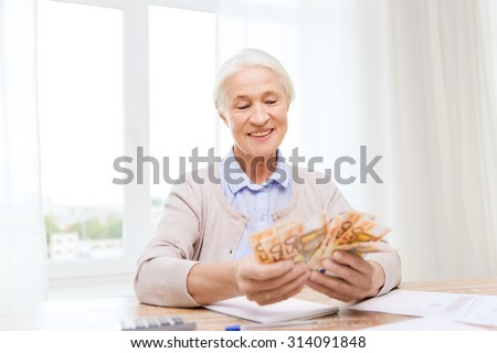 business, savings, annuity insurance, age and people concept - happy senior woman with calculator and bills counting euro money at home - stock photo