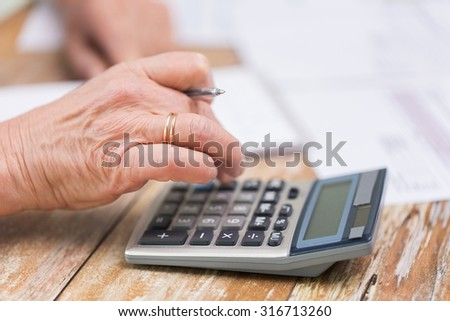 business, savings, annuity insurance, age and people concept - senior woman with calculator and papers counting at home - stock photo