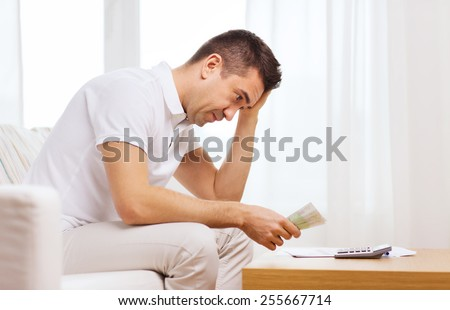 business, savings, financial crisis and people concept - man with money and calculator at home - stock photo