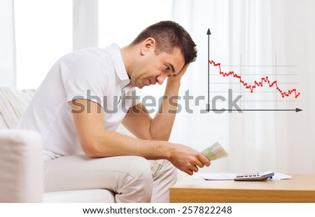 business, savings, financial crisis and people concept - upset man with money and calculator at home - stock photo