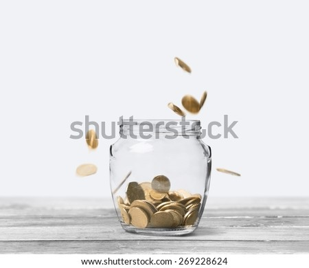Business. Savings rate concept - jars in row filling up with falling coins, focus on middle jar - stock photo