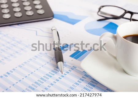Business scene: calculator and a pen over business documents - stock photo