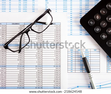 Business scene: calculator, eyeglasses and financial charts - stock photo