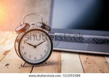 business schedule concept with black alarm clock with blank screen notebook or laptop on wooden floor with free copy space for yout text ideas