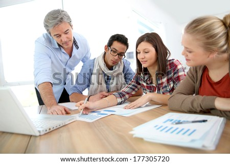 Business school students in marketing class with teacher - stock photo