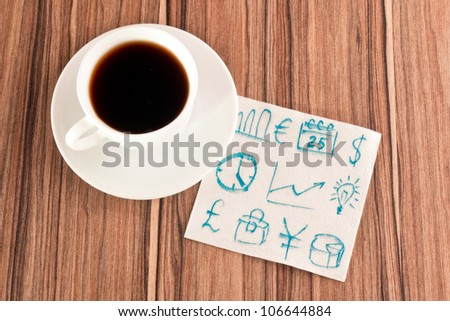 Business signs on a napkin and cup of coffee - stock photo