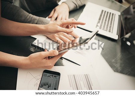 Business situation,meeting of financial analysts.Photo woman showing marketing reports tablet.Modern smartphone and laptop on table.Working process office, discussion startup. Horizontal. Film effect