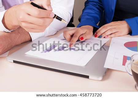 Business situation,team work,brainstorming. Photo female hand holding pen. Man using smartphone and modern laptop. Working process office. Discussion startup. Horizontal.Blurred,film effect