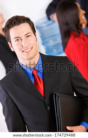 Business: Smiling Businessman With Group Around Water Cooler - stock photo