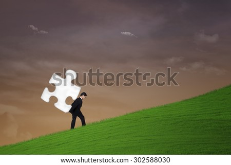 Business solution concept: Businessman is carrying a puzzle under sunset sky - stock photo