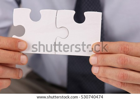 Business solutions, partnership concept. Businessman holding two pieces of a blank puzzle