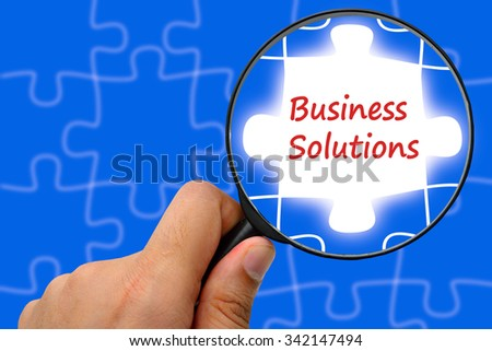 Business solutions word. Magnifier and puzzles. - stock photo