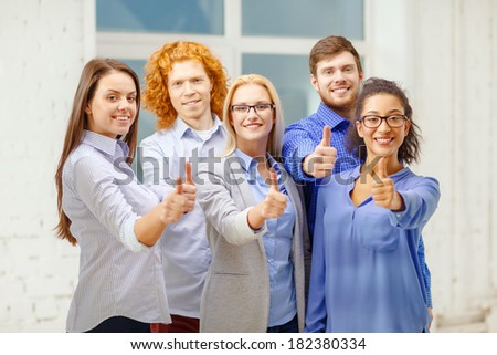 business, startup and office concept - happy creative team showing thumbs up in office - stock photo