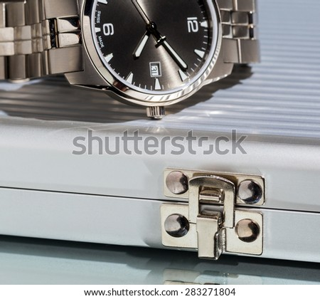 Business still-life, a fragment of a wristwatch, metal case on bright background.