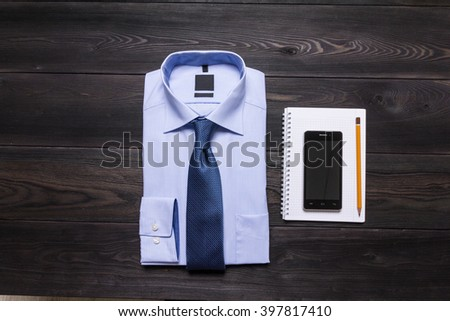 Business still life. Blue folded shirt, necktie, spiral notebook, yellow pencil, smartphone on black wooden textured table - stock photo