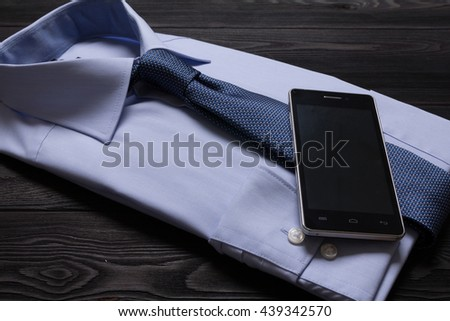 business still life. Blue formal shirt and mans tie and celiphone. - stock photo