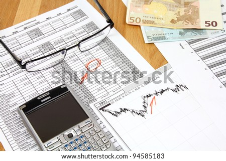 Business still life. Financial analysis - income statement, finance graphs, generic smart phone and Euro money - stock photo