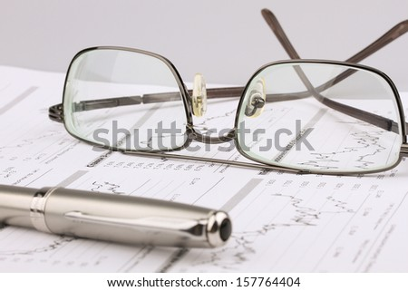 Business still-life from the table, eyeglasses, ink pen - stock photo