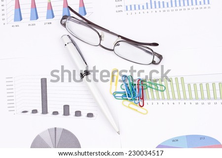 Business still-life of a black pen, graphs, eyeglasses, paperclips