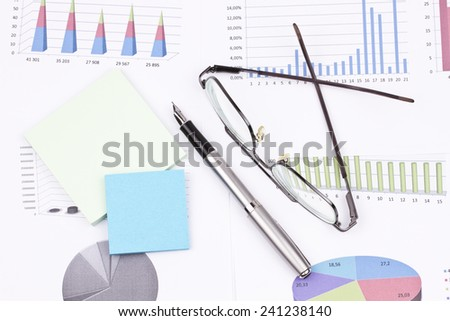 Business still-life of a ink pen, sticker, graphs, eyeglasses