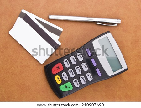 Business still-life of a payment terminal, credit cards, pen - stock photo