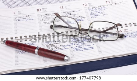 Business still-life of a pen, charts, eyeglasses, diary