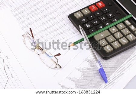 Business still-life of a pen, pencil, charts, eyeglasses, calculator