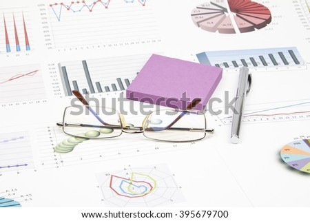 Business still-life of a pen, sticker, graphs, eyeglasses