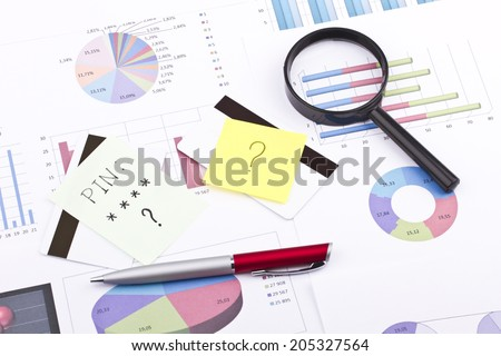 Business still-life of a pen, sticker, graphs, eyeglasses, credit card, magnifier - stock photo