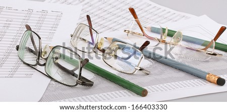 Business still-life of a pencil, charts, eyeglasses