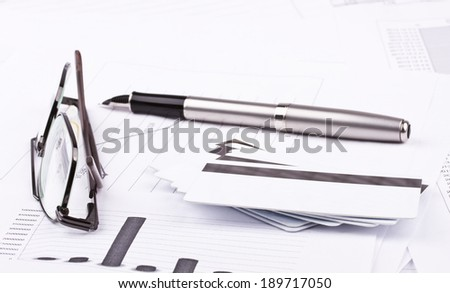 Business still-life of ink pen, charts, tables, eyeglasses, credit Cards - stock photo