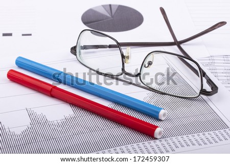 Business still-life of marker, charts, eyeglasses, graphs