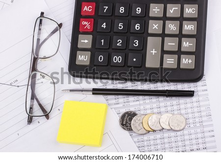Business still-life of pen, charts, calculator, tables, stickers, eyeglasses, coins