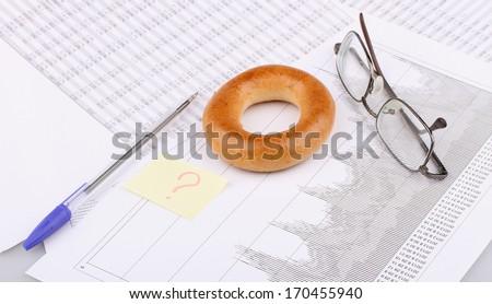 Business still-life of pen, charts, eyeglasses, breakfast - stock photo