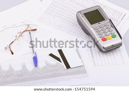 Business still-life of pen, charts, tables, eyeglasses, payment terminal, credit Cards