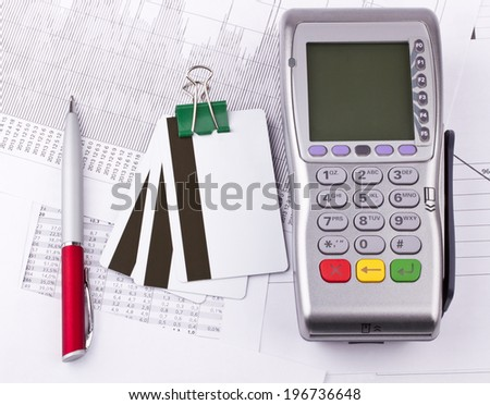 Business still-life of tables, payment terminal, credit Cards, paperclip, pen - stock photo
