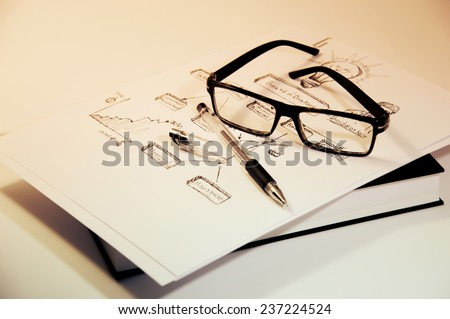Business still life, warm sepia color style. Close up of a pair of reading glasses and a black pen and book. - stock photo