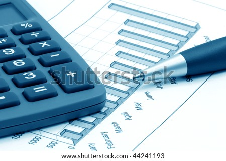 Business still-life with calculator, pen and diagram (blue toned)