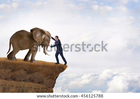 business strength concept businessman pushed to the edge of a cliff by an elephant - stock photo