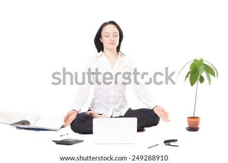Business, study, healthy lifestyle, work at home. Serene young businesswoman surrounded by office accessories, relaxing, meditating in yoga Padmasana (Lotus Pose) in front of laptop, isolated - stock photo