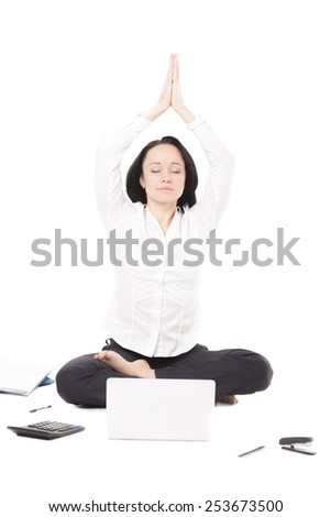 Business, study, healthy lifestyle, work at home. Serene young female professional surrounded by office accessories meditating in yoga Padmasana (Lotus Pose) in front of laptop, isolated - stock photo
