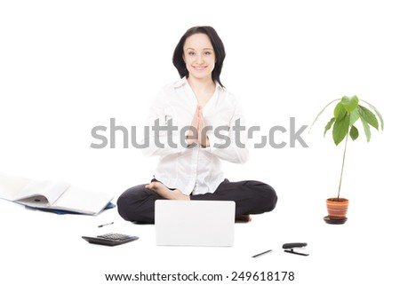 Business, study, healthy lifestyle, work at home. Serene young female worker surrounded by office accessories meditating in yoga Padmasana (Lotus Pose) palms touching in a gesture of namaste, isolated - stock photo